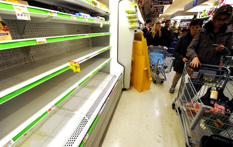 Customers shop for food at a Supermarket in Manhattan, Sunday, Oct. 28, 2012, in New York. Tens of thousands of people were ordered to evacuate coastal areas Sunday as big cities and small towns across the U.S. Northeast braced for the onslaught of a superstorm threatening some 60 million people along the most heavily populated corridor in the nation. (AP Photo/ Louis Lanzano)