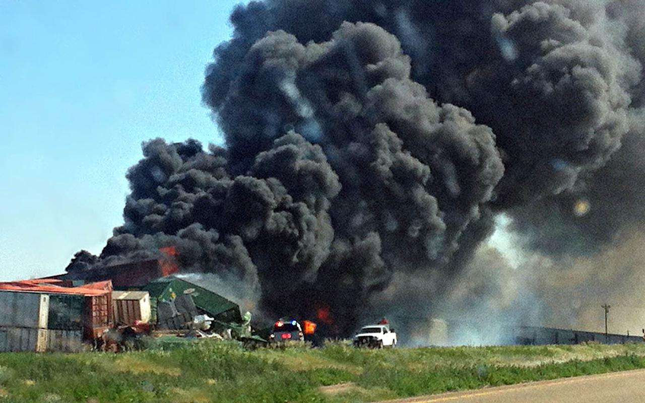 Smoke rises from two cargo trains that collided two miles east of Goodwell, Okla. on Sunday, June 24, 2012. A total of four people were on the trains, and one was reportedly killed in the accident. (AP Photo/The Guymon Daily Herald, Trudy Hart)