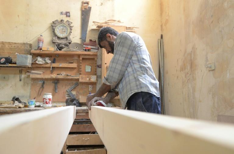 A Syrian furniture worker measures wood at Yussef al-Qabuni's workshop