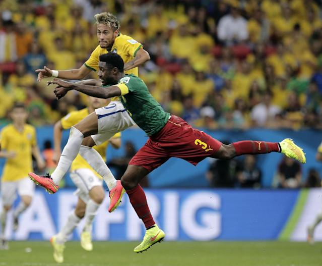 Cameroon's Nicolas N'Koulou leaps against Brazil's Neymar to clear the ball during the group A World Cup soccer match between Cameroon and Brazil at the Estadio Nacional in Brasilia, Brazil, Monday, June 23, 2014. (AP Photo/Bernat Armangue)