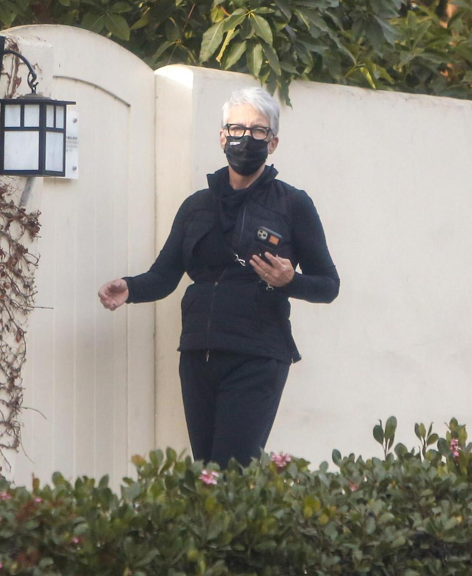 <p>Jamie Lee Curtis masks up for a solo stroll on Wednesday around her neighborhood in L.A. </p>