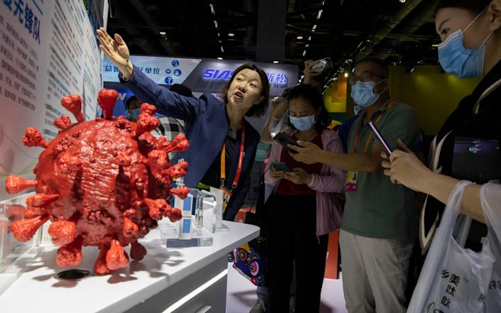 An employee answers questions from the public near samples of a COVID-19 vaccine produced by Sinopharm subsidiary CNBG - AP