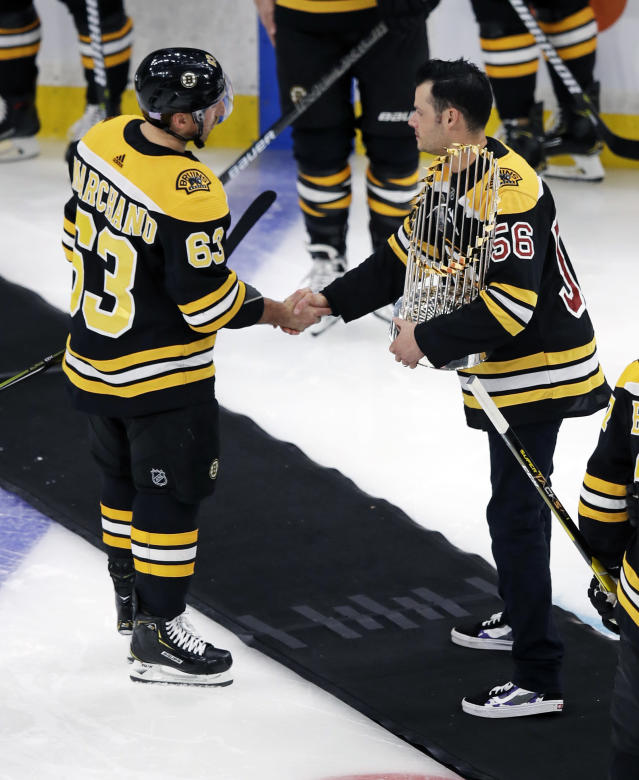 Boston Red Sox pitcher Joe Kelly, right, holds the 2018 World Series championship trophy as he shakes hands with Boston Bruins left wing Brad Marchand (63) prior to a hockey game in Boston, Monday, Nov. 5, 2018. (AP Photo/Charles Krupa)
