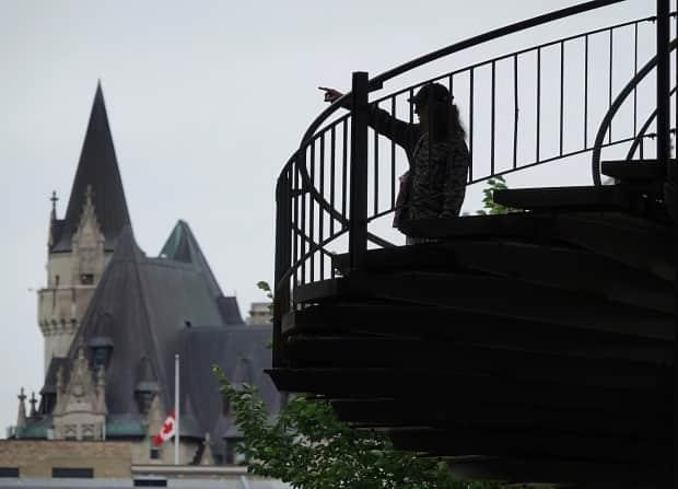A silhouetted person points into the distance from a staircase near Parliament Hill in Ottawa on July 15, 2021. (Ian Black/CBC - image credit)