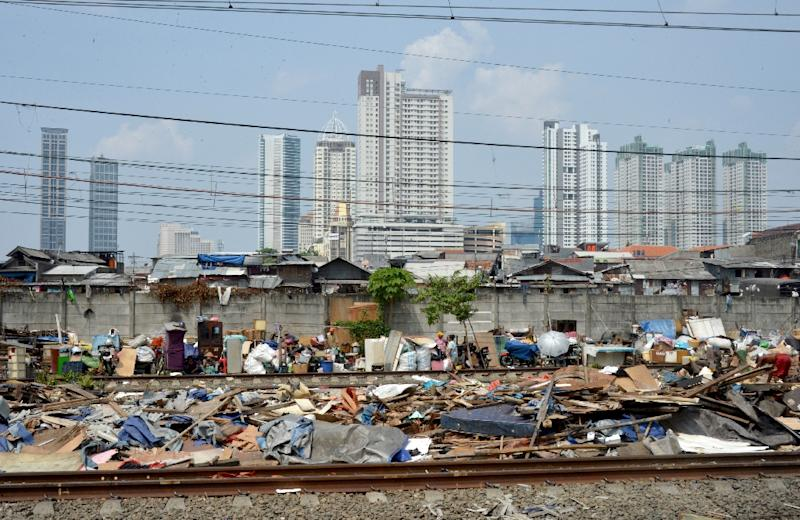 Indonesian slum dwellers dismantle their shanty houses along railroad tracks in Jakarta on August 8, 2014 ahead of a projected upgrade of the service