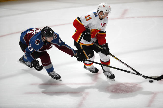 Colorado Avalanche center Nathan MacKinnon, left, reaches for the puck as Calgary Flames center Mikael Backlund moves down the ice during the first period of Game 4 of an NHL hockey playoff series Wednesday, April 17, 2019, in Denver. (AP Photo/David Zalubowski)