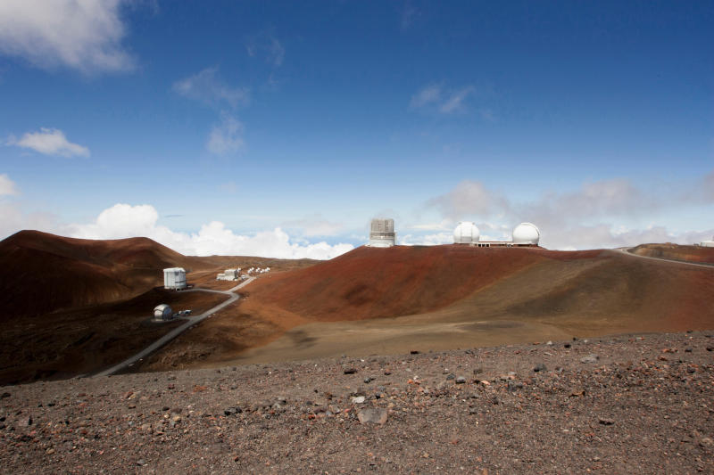 FILE - In this Aug. 31, 2015, file photo, observatories and telescopes sit atop Mauna Kea, Hawaii's tallest mountain and the proposed construction site for a new $1.4 billion telescope, near Hilo, Hawaii. Construction on a giant telescope will start again next week after lengthy court battles and passionate protests from those who say building it on Hawaii's tallest mountain will desecrate land sacred to some Native Hawaiians. State officials announced Wednesday, July 10, 2019, that the road to the top of Mauna Kea mountain on the Big Island will be closed Monday as equipment is delivered to the construction site. (AP Photo/Caleb Jones, File)