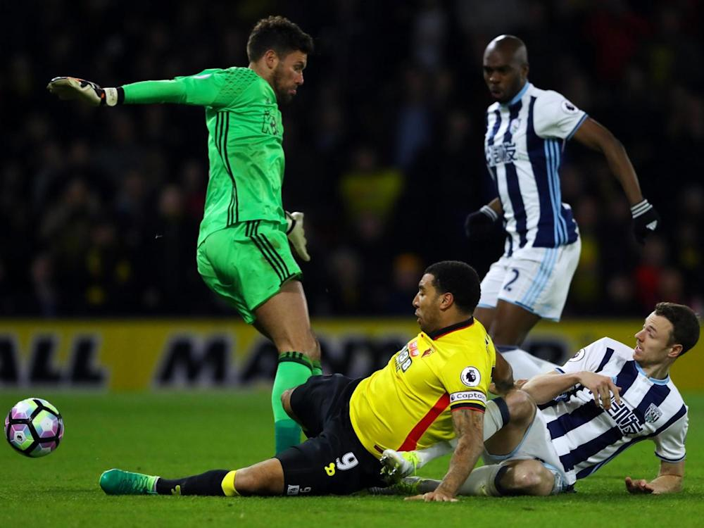 Deeney bundles the ball past Foster to help win Watford all three points (Getty)