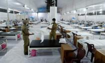 Workers prepare a bed at a recently constructed quarantine facility for patients diagnosed with the coronavirus disease (COVID-19) in Mumbai