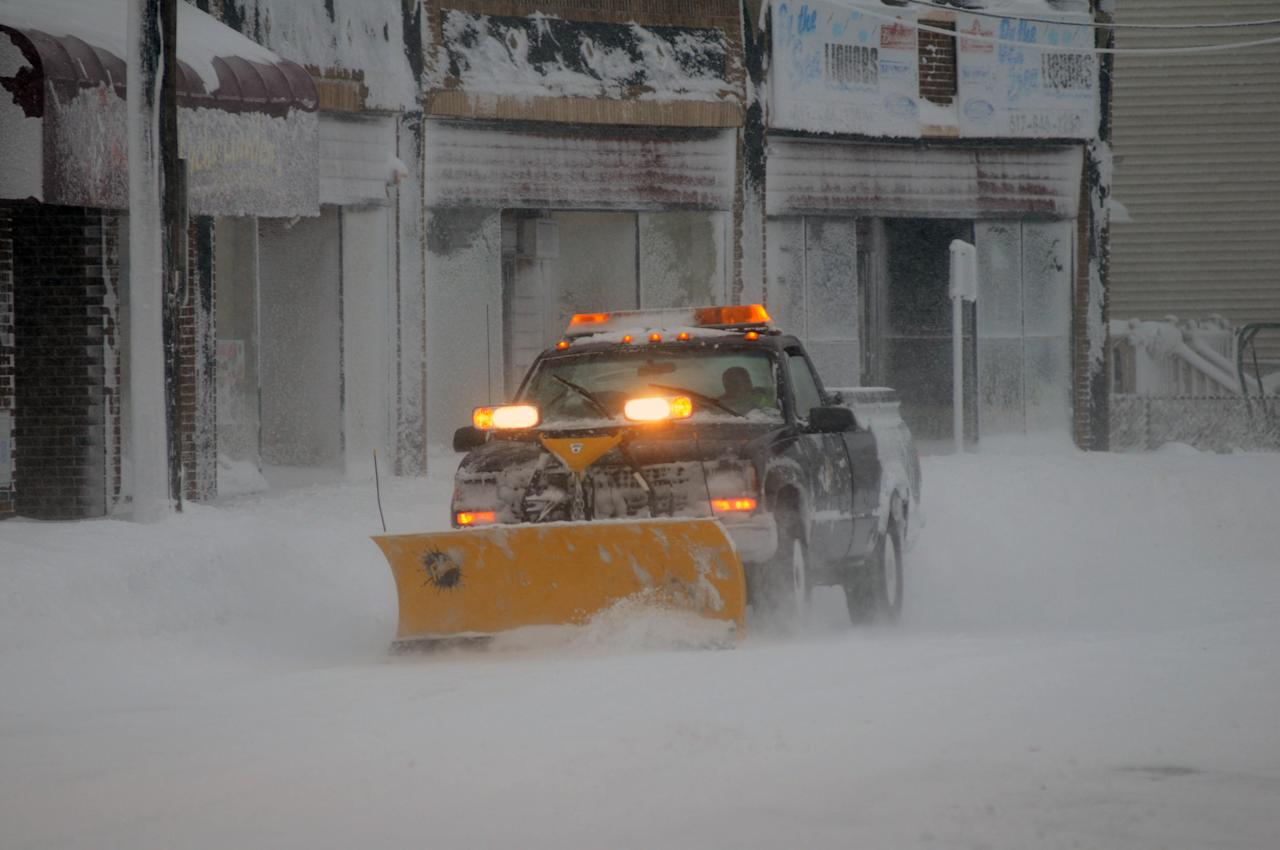 WINTHROP, MA - FEBRUARY 9: A snow plow drives along Shirley Street on February 9, 2013 in Winthrop, Massachusetts.  The powerful storm has knocked out power to 650,000 and dumped more than two feet of snow in parts of New England.  (Photo by Darren McCollester/Getty Images)