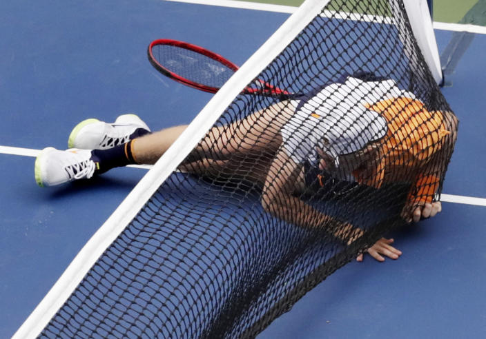 Denis Shapovalov, of Canada, falls into the net against Kevin Anderson, of South Africa, during the third round of the U.S. Open tennis tournament, Friday, Aug. 31, 2018, in New York. (AP Photo/Julio Cortez)