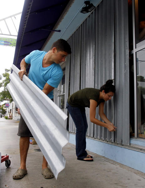 Yoni Haim, left, and Jessica Yeshalek board their storefront as they prepare for Tropical Storm Isaac, Saturday, Aug. 25, 2012. Isaac's winds are expected to be felt in the Florida Keys by sunrise Sunday morning. (AP Photo/Alan Diaz)