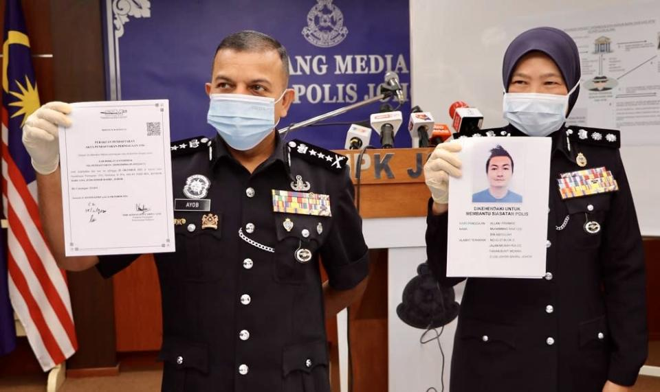 Johor police chief Datuk Ayob Khan Mydin Pitchay (left) holds a document detailing the investigation into the syndicate's activities. — Picture courtesy of the Johor police contingent headquarters