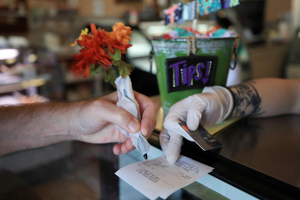 NEW ORLEANS, LA  - MARCH 19: A patron uses a pen wrapped in paper to sign a credit card receipt at Angelo Brocato's Italian Ice Cream Parlor due to the coronavirus (COVID-19) on March 19, 2020 in New Orleans, Louisiana. St. Joseph's day, commemorated for the Catholic Saint who protects communities during times of famine and sickness is usually celebrated with altars, food and a parade, canceled this year because of the coronavirus.  (Photo by Chris Graythen/Getty Images)