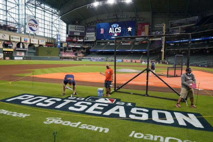 Grounds crew personnel apply the final touches to a postseason field logo at Minute Maid Park before baseball practice in Houston, Thursday, Oct. 14, 2021. The Houston Astros host the Boston Red Sox in Game 1 of the American League Championship Series on Friday. (AP Photo/Tony Gutierrez)