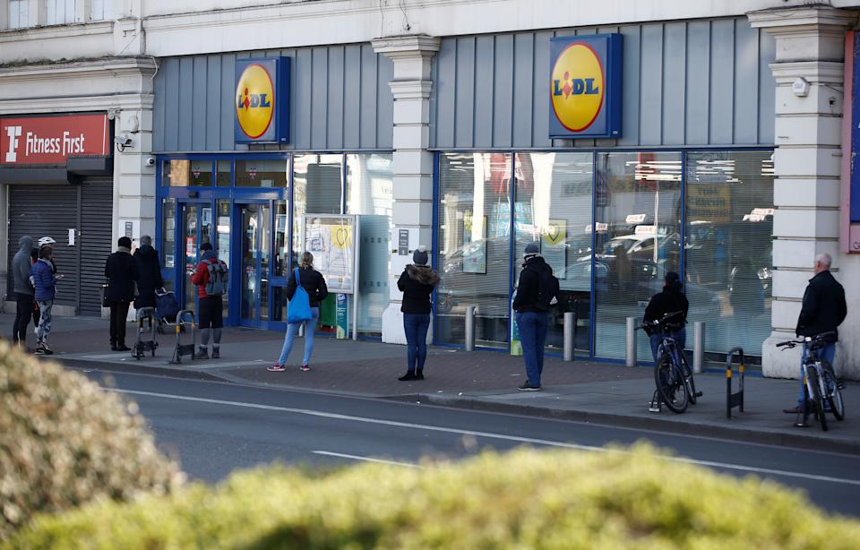 People follow social distancing rules while they queue outside a Lidl store in South London as the spread of the coronavirus disease (COVID-19) continues, in London, Britain, March 27, 2020. REUTERS/Henry Nicholls