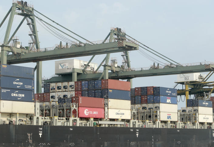 FILE - In this May 3, 2020, file photo, containers are loaded on a ship at the Saigon port in Ho Chi Minh City, Vietnam. The World Bank on Tuesday, Sept. 28, 2021, cut its economic growth forecast for developing countries in East Asia due to the impact of the coronavirus's delta variant and called on governments to help the poor and small businesses avoid long-term damage. (AP Photo/Hau Dinh, File)
