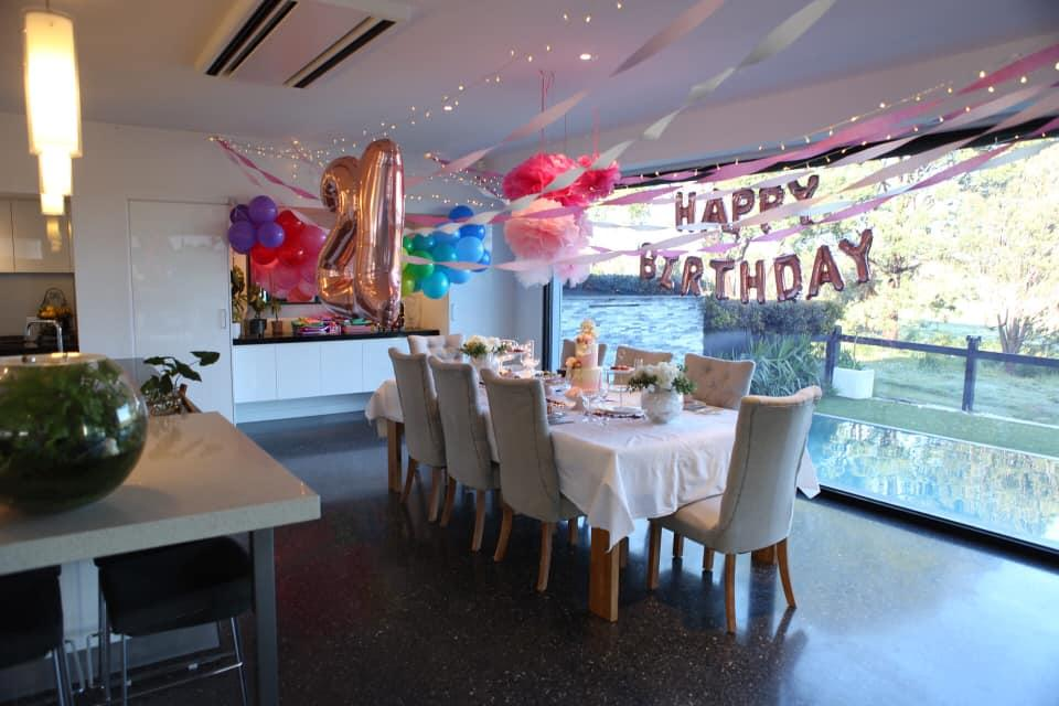A dining room decorated for a girl's 21st birthday party