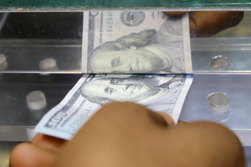 Man inserts a U.S. dollar banknote into the window of a local currency exchange in Aden