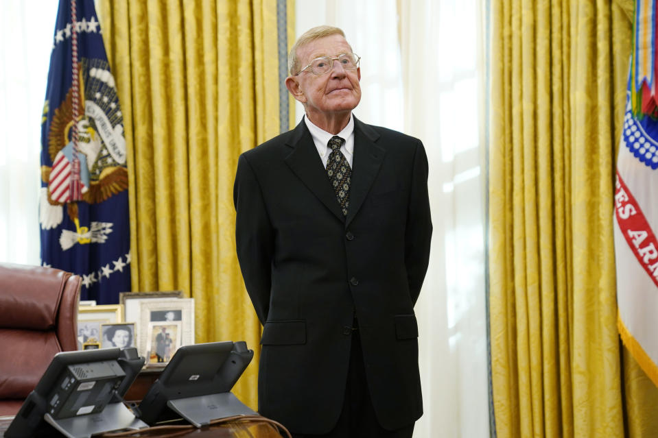 Former college coach Lou Holtz listens to President Donald Trump speak before being awarded the medal of Freedom, the highest civilian honor, in the Oval Office at the White House, Thursday, Dec. 3, 2020, in Washington. Holtz had a storied 34-year coaching career that included winning the 1988 national title at the University of Notre Dame. (AP Photo/Evan Vucci)