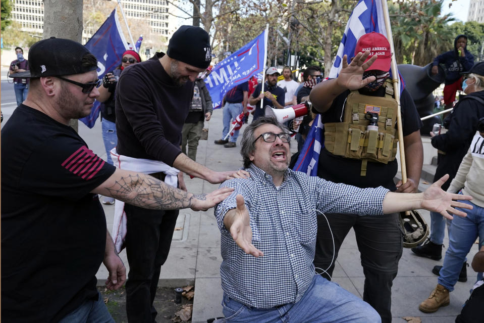 Demonstrators pray during a pro-Trump rally outside of City Hall Wednesday, Jan. 6, 2021, in Los Angeles. Demonstrators, supporting President Donald Trump, are gathering in various parts of Southern California as Congress debates to affirm President-elect Joe Biden's electoral victory. (AP Photo/Marcio Jose Sanchez)