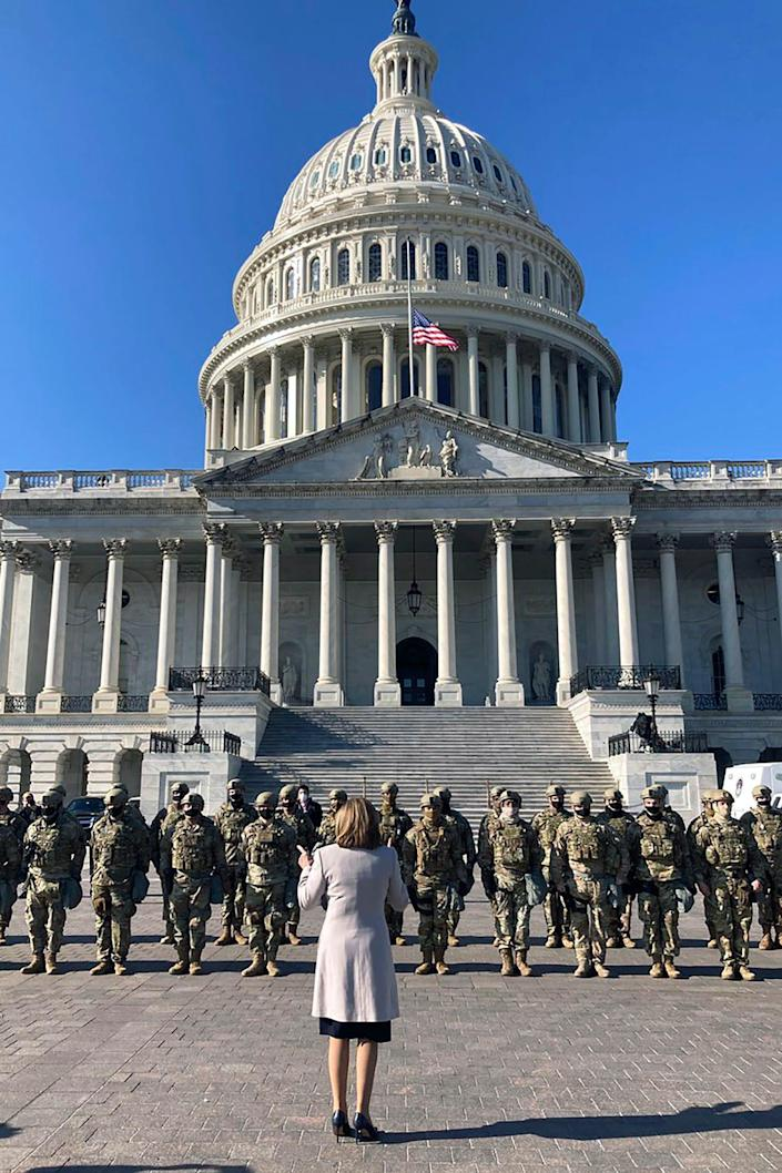In this image released by the Speaker of the House Nancy Pelosi's Office, Pelosi speaks to National Guard troops outside the U.S. Capitol on Wednesday, Jan. 13, 2021, in Washington.