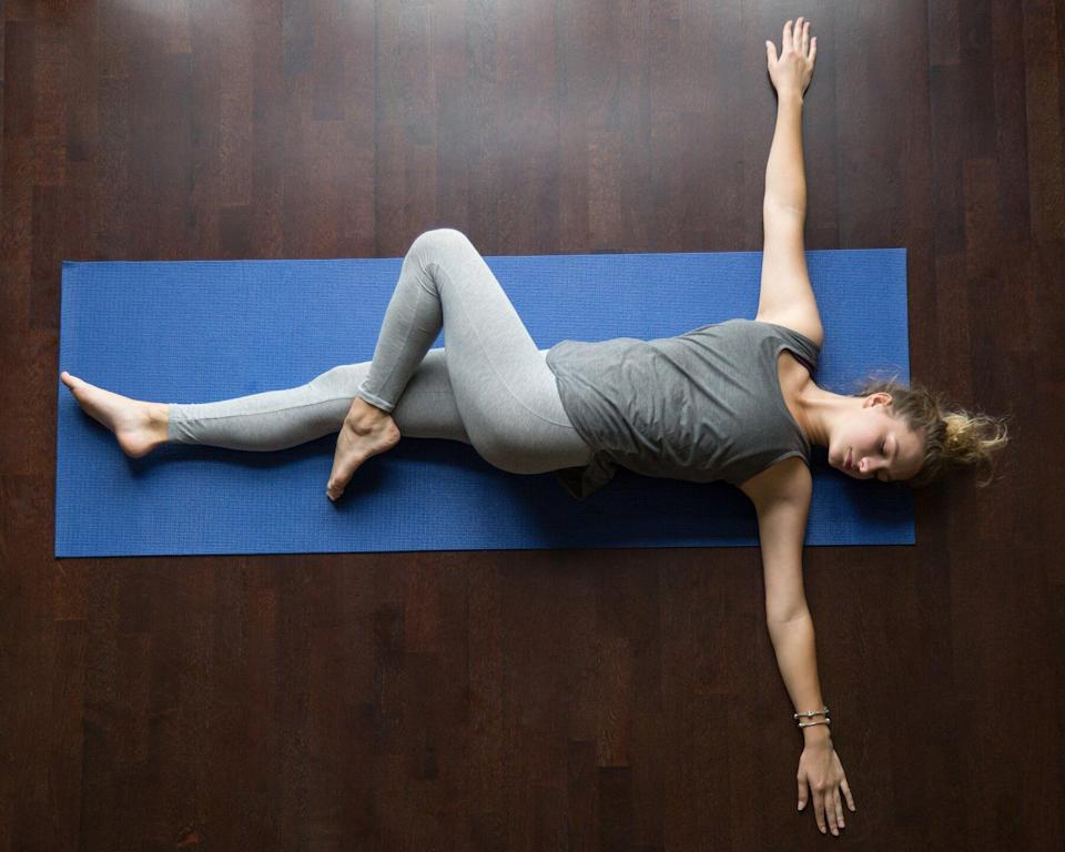 Yoga Poses for Digestion: Woman doing supine spinal twist yoga pose