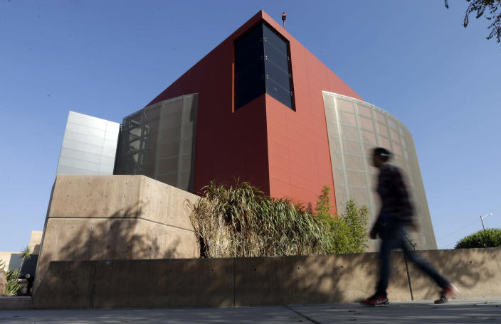 """In this Friday, Dec. 7, 2012 photo, a man walks past an expansion of the Tijuana Cultural Center known as """"The Cube,"""" designed by architect Eugenio Velazquez, in Tijuana, Mexico. Velazquez doesn't fit the mold of the down-on-his luck, uneducated, underemployed courier who ferries drugs to the United States for Mexican drug cartels. Yet, now he awaits sentencing in San Diego for concealing 12.8 pounds of cocaine while entering the U.S. (AP Photo/Gregory Bull)"""