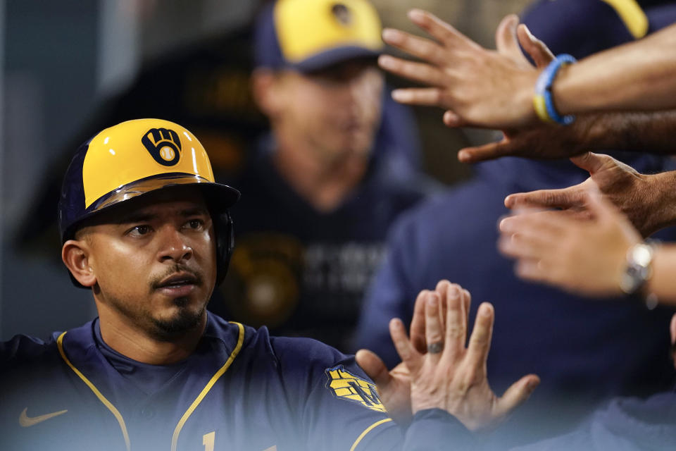 Milwaukee Brewers' Eduardo Escobar celebrates in the dugout after scoring during the second inning of a baseball game against the Los Angeles Dodgers Friday, Sept. 1, 2021, in Los Angeles. (AP Photo/Ashley Landis)