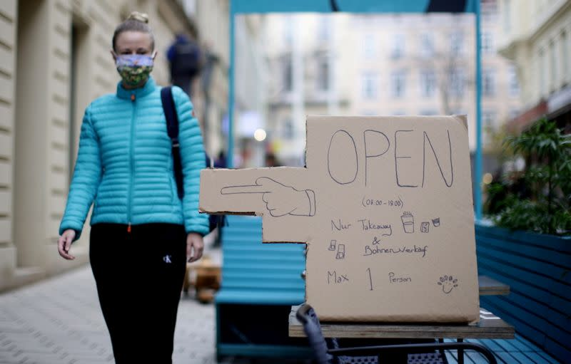 A woman walks past a sign marking a coffee shop open for take away during lockdown