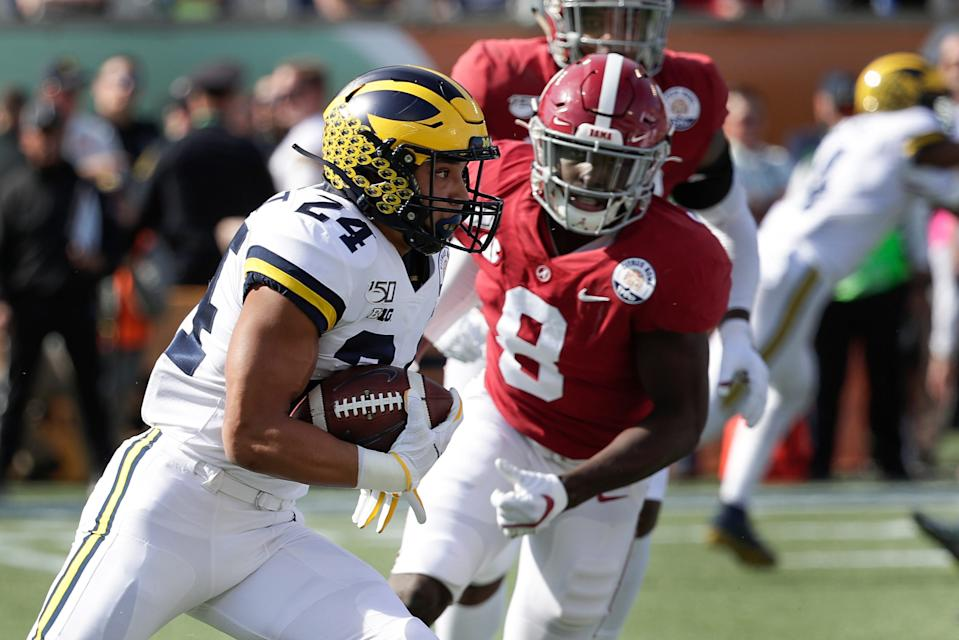 Michigan's Zach Charbonnet runs for yardage past Alabama linebacker Christian Harris during the first half of the Citrus Bowl, Jan. 1, 2020, in Orlando, Fla.