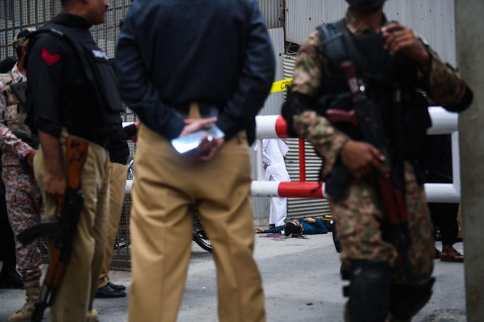 EDITORS NOTE: Graphic content / Police and paramilitary soldiers guard near a body of an alleged gunman at the main entrance of the Pakistan Stock Exchange building in Karachi on June 29, 2020. - Gunmen attacked the Pakistan Stock Exchange in Karachi on June 29, with four of the assailants killed, police said. (Photo by Asif HASSAN / AFP) (Photo by ASIF HASSAN/AFP via Getty Images)