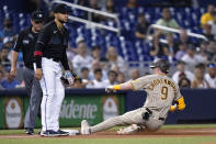 San Diego Padres' Jake Cronenworth (9) beats the throw to Miami Marlins third baseman Isan Diaz for a triple during the first inning of a baseball game Friday, July 23, 2021, in Miami. (AP Photo/Lynne Sladky)