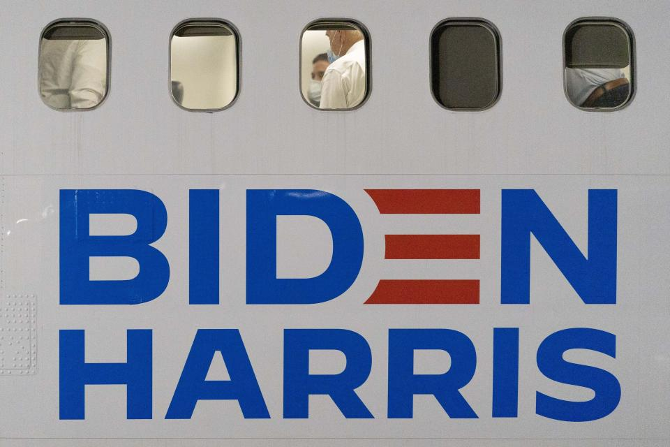 Democratic presidential candidate former Vice President Joe Biden, center, sits aboard his campaign plane as he arrives at New Castle Airport in New Castle, Del., Tuesday, Oct. 27, 2020, after attending rallies in Georgia. (AP Photo/Andrew Harnik)