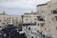 Thousands of ultra-Orthodox Jews participate in the funeral of prominent rabbi Meshulam Soloveitchik, flouting the country's ban on large public gatherings amid the pandemic, in Jerusalem, Sunday, Jan. 31, 2021. (AP Photo/Ariel Schalit)