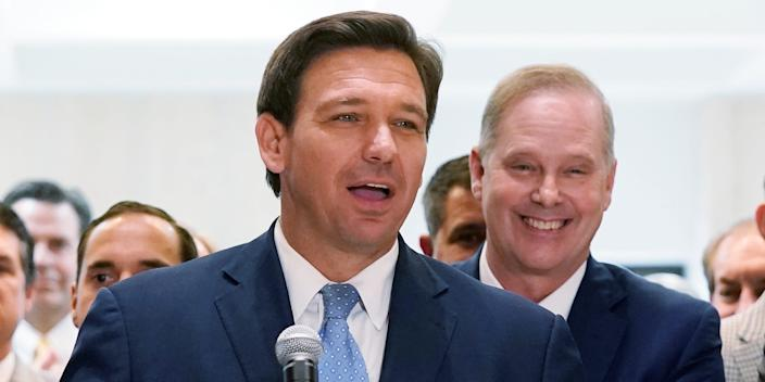 Gov. Ron DeSantis surrounded by lawmakers at the Tallahassee Capitol.