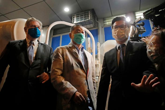 Media tycoon and newspaper founder Jimmy Lai, center, leaves a police station in Hong Kong on Aug. 12, 2020.