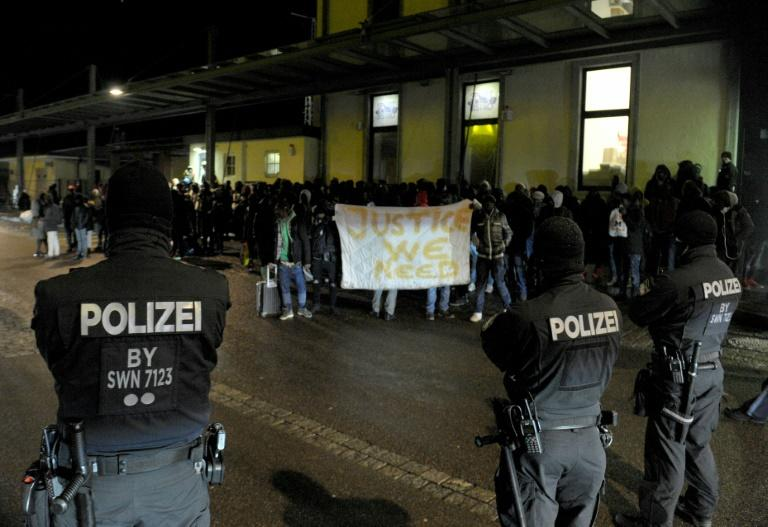 Refugees, mainly rejected asylum seekers, hold a banner reading 'Justice we need' as they face police officers at a train station in southern Germany