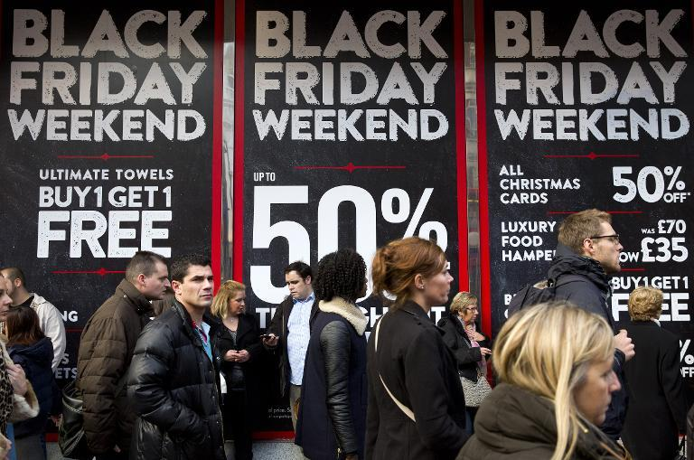 Shoppers are pictured walking past 'Black Friday' advertising in shop windows on Oxford Street in central London on November 28, 2014