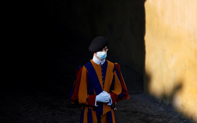 A Swiss guard wearing a protective face mask is seen at the San Damaso courtyard ahead of the weekly general audience at the Vatican, September 16 - REUTERS/Yara Nardi/File Photo