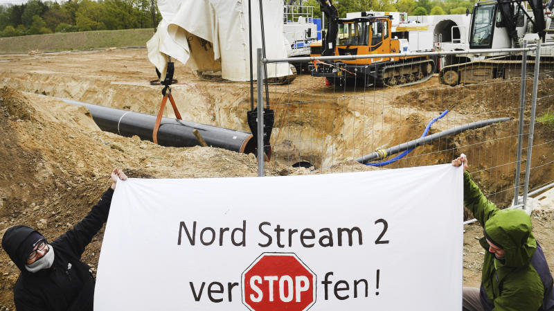 Activists occupy a German pipeline building site in Wrangelsburg, northern Germany, Thursday, May 16, 2019. Police say activists have occupied a building site in northern Germany to protest against the ongoing Nord Stream 2 pipeline project with Russia. The sign reads 'Nord Stream 2 plug of'. (Stefan Sauer/dpa via AP)