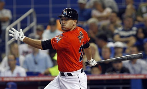 Miami Marlins' Greg Dobbs follows through on a double against the Miami Marlins in the third inning of a baseball game in Miami, Thursday, April 19, 2012. Hanley Ramirez and Logan Morrison scored on the double. (AP Photo/Alan Diaz)