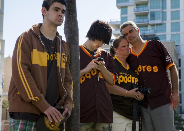 Alex Mcbrayer, 16, Trevor Herman, 17, Rebecca Herman, 54 and her friend Wayne Mcbrayer, 48, mourn at a makeshift memorial to former San Diego Padres outfielder Tony Gwynn at Petco Park in San Diego, California June 16, 2014. Gwynn, one of the greatest hitters of his generation, died on Monday at age 54 after a battle with cancer, the National Baseball Hall of Fame and Museum said. REUTERS/Sam Hodgson (UNITED STATES - Tags: SPORT BASEBALL OBITUARY)