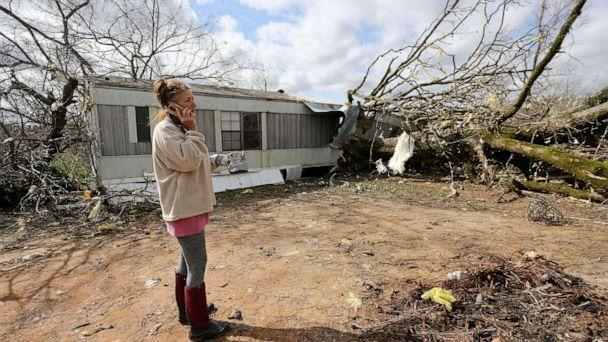 PHOTO: Jennifer Patterson talks on her cell phone outside her destroyed mobile home in Tuscaloosa County, Alabama, March 18, 2021. (Tuscaloosa News via USA Today Network)