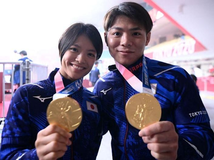 Uta Abe and Hifumi Abe hold their gold medals at the Tokyo Olympics