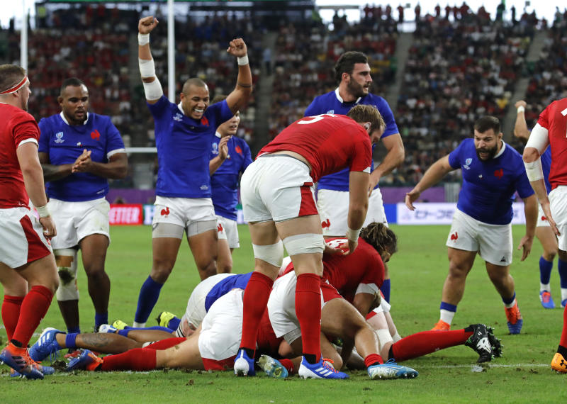 France's Sebastien Vahaamahina, at bottom, scores a try during the Rugby World Cup quarterfinal match against Wales at Oita Stadium in Oita, Japan, Sunday, Oct. 20, 2019. (AP Photo/Christophe Ena)