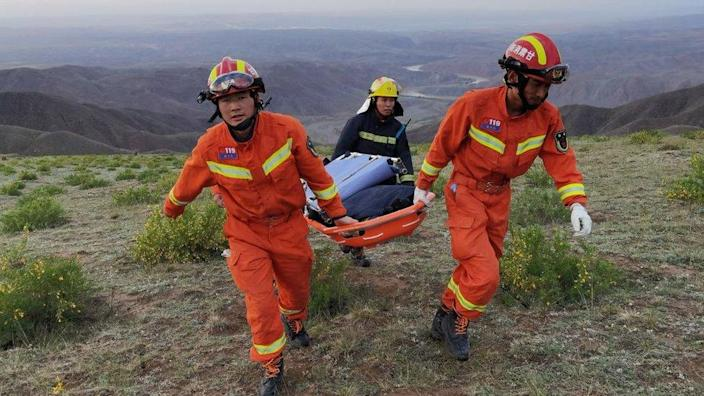 Rescuers carrying equipment as they search for runners who were competing in a 100-kilometre cross-country mountain race when extreme weather hit the area