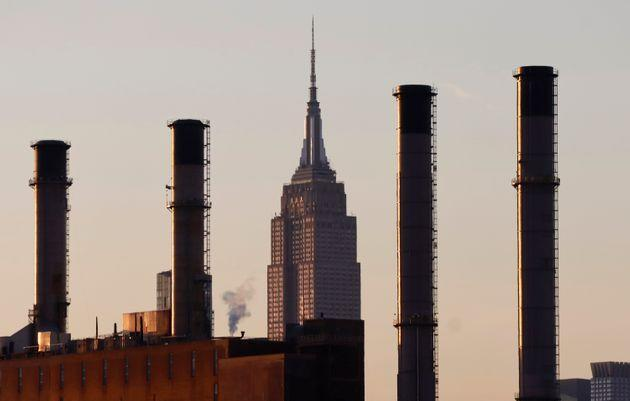 The sun sets on the Empire State Building as it sits behind smoke stacks of a ConEdison power plant. (Photo: Gary Hershorn via Getty Images)