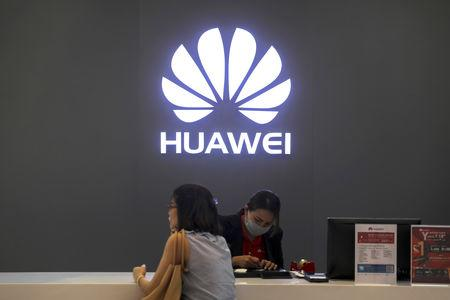 FILE PHOTO - A woman sits next to a salesperson at a Huawei shop in Bangkok, Thailand