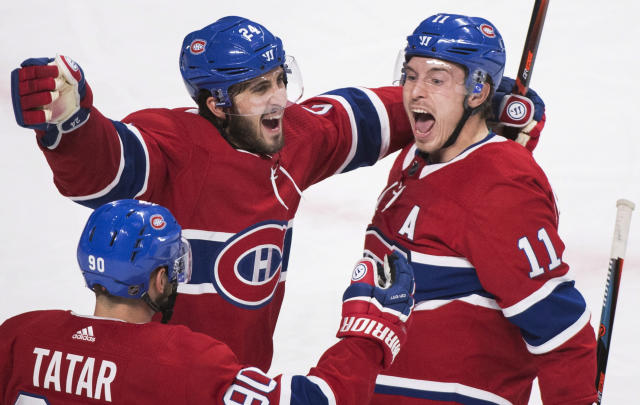 Montreal Canadiens' Brendan Gallagher (11) celebrates with teammates Phillip Danault (24) and Tomas Tatar after scoring against the St. Louis Blues during the third period of an NHL hockey match, in Montreal, Wednesday, Oct. 17, 2018. (Graham Hughes/The Canadian Press via AP)